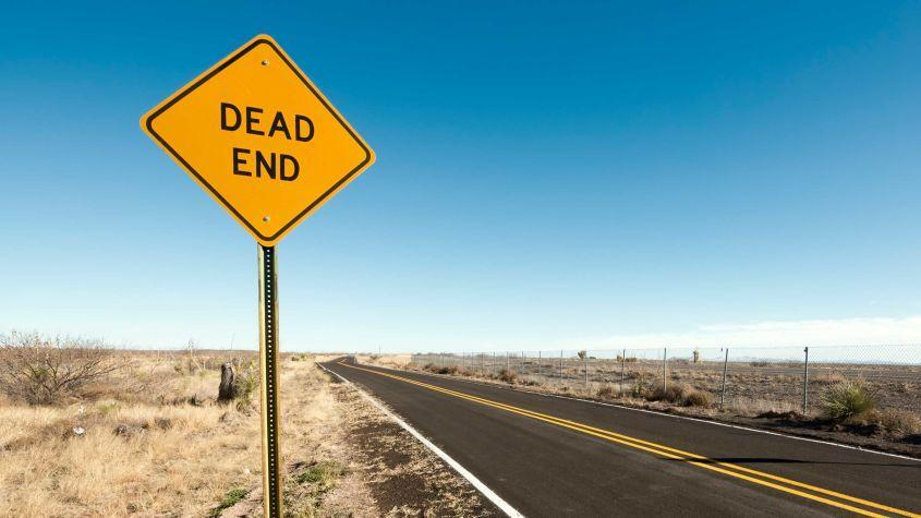 A dead end sign on a desolate road.
