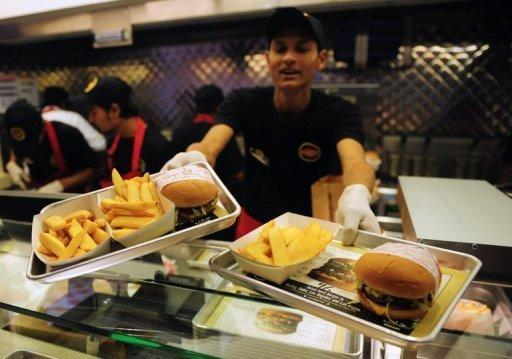 A Pakistani Fatburger employee serves burgers to a customer in Karachi on January 10, 2013