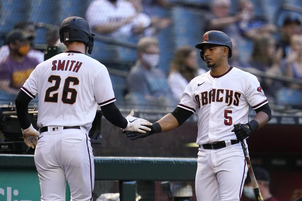 Arizona Diamondbacks' Pavin Smith (26) celebrates his run scored against the Miami Marlins with teammate Eduardo Escobar (5) during the first inning of a baseball game Monday, May 10, 2021, in Phoenix. (AP Photo/Ross D. Franklin)