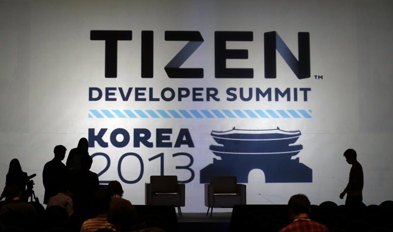 In this Monday, Nov. 11, 2013 photo, participants are seen near the logo of Tizen during the Tizen Developer Summit 2013 in Seoul, South Korea. South Korean electronics giant Samsung Electronics Co. is in a quiet push to make its Tizen operating system a part of the technology lexicon as familiar as Google's Android or Apple's iOS. Its ambition doesn't stop there. Samsung sees the software in your car, fridge and television too. The first developer conference in Asia for Tizen wrapped up Tuesday after a two-day run, bringing together app developers and Tizen backers from Samsung, Intel and mobile operators. (AP Photo/Lee Jin-man)