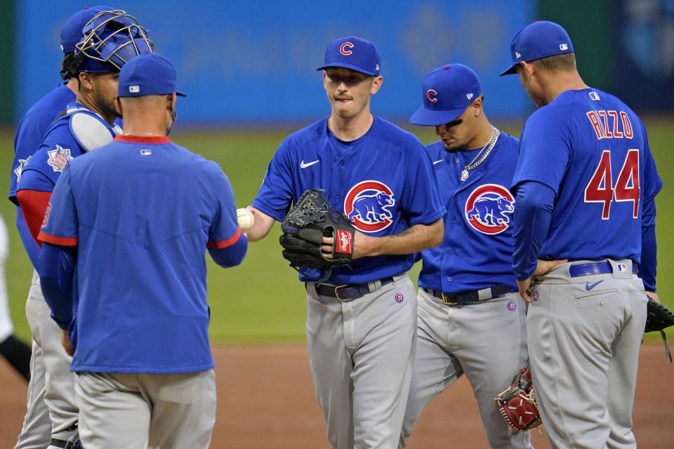 Chicago Cubs starting pitcher Zach Davies, center, hands the ball to manager David Ross as he leaves the baseball game against the Pittsburgh Pirates during the second inning in Pittsburgh, Saturday, April 10, 2021. (AP Photo/Gene J. Puskar)