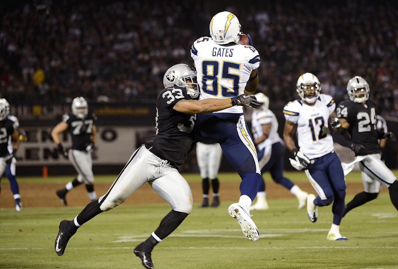 OAKLAND, CA - SEPTEMBER 10:  Antonio Gates #85 of the San Diego Chargers catches a seventeen yard pass over Tyvon Branch #33 of the Oakland Raiders in the second quarter of the season opener at Oakland-Alameda County Coliseum on September 10, 2012 in Oakland, California.  (Photo by Thearon W. Henderson/Getty Images)