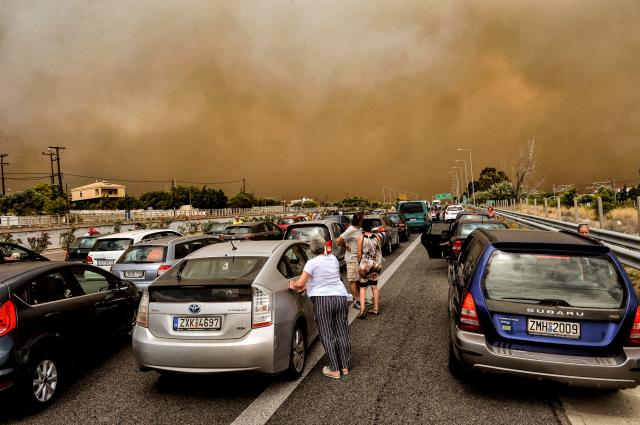 <p>Cars are blocked at the closed National Road during a wildfire in Kineta, near Athens, on July 23, 2018. (Photo: Valerie Gache/AFP/Getty Images) </p>