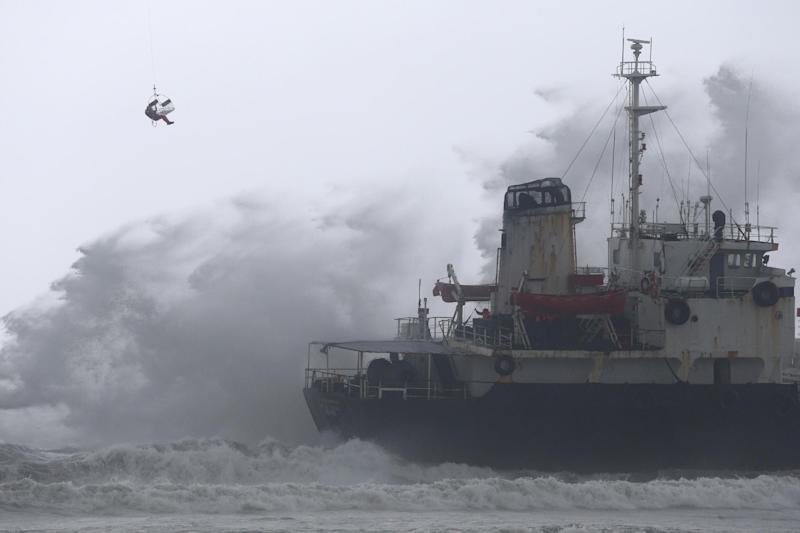 A Chinese worker is lifted from a helicopter near the Sheng Chang oil tanker after it ran aground at Kaohsiung harbor as Typhoon Matmo hit on July 23, 2014