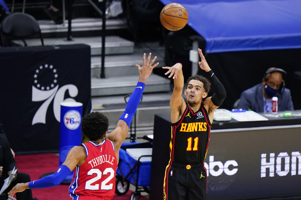 Atlanta Hawks' Trae Young (11) goes up for a shot against Philadelphia 76ers' Matisse Thybulle (22) during Game 1 of a second-round NBA basketball playoff series, Sunday, June 6, 2021, in Philadelphia. Young became the second player in NBA history to score 30 points in each of his first four career playoff road games. The latest came in Atlanta's surprising Game 1 victory in Philadelphia. (AP Photo/Matt Slocum)