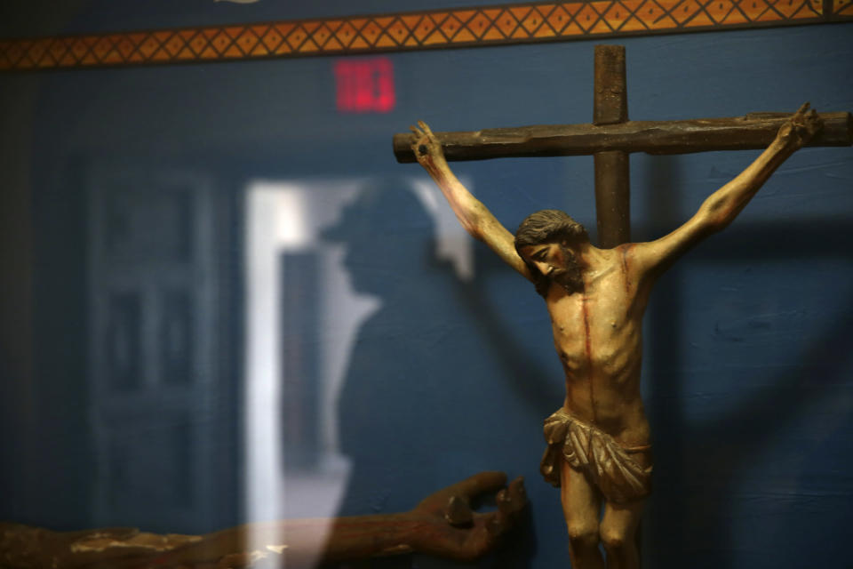 A man is reflected in a glass case containing a statue of a crucified Jesus Christ at the museum of the Mission San Xavier del Bac in Tucson, Ariz., Friday, Feb. 21, 2020. San Xavier was founded as a Catholic mission by Father Eusebio Kino in 1692 when Southern Arizona was part of New Spain. (AP Photo/Dario Lopez-MIlls)