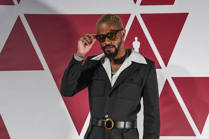 Lakeith Stanfield wearing a Saint Laurent jumpsuit over a shirt with an open collar