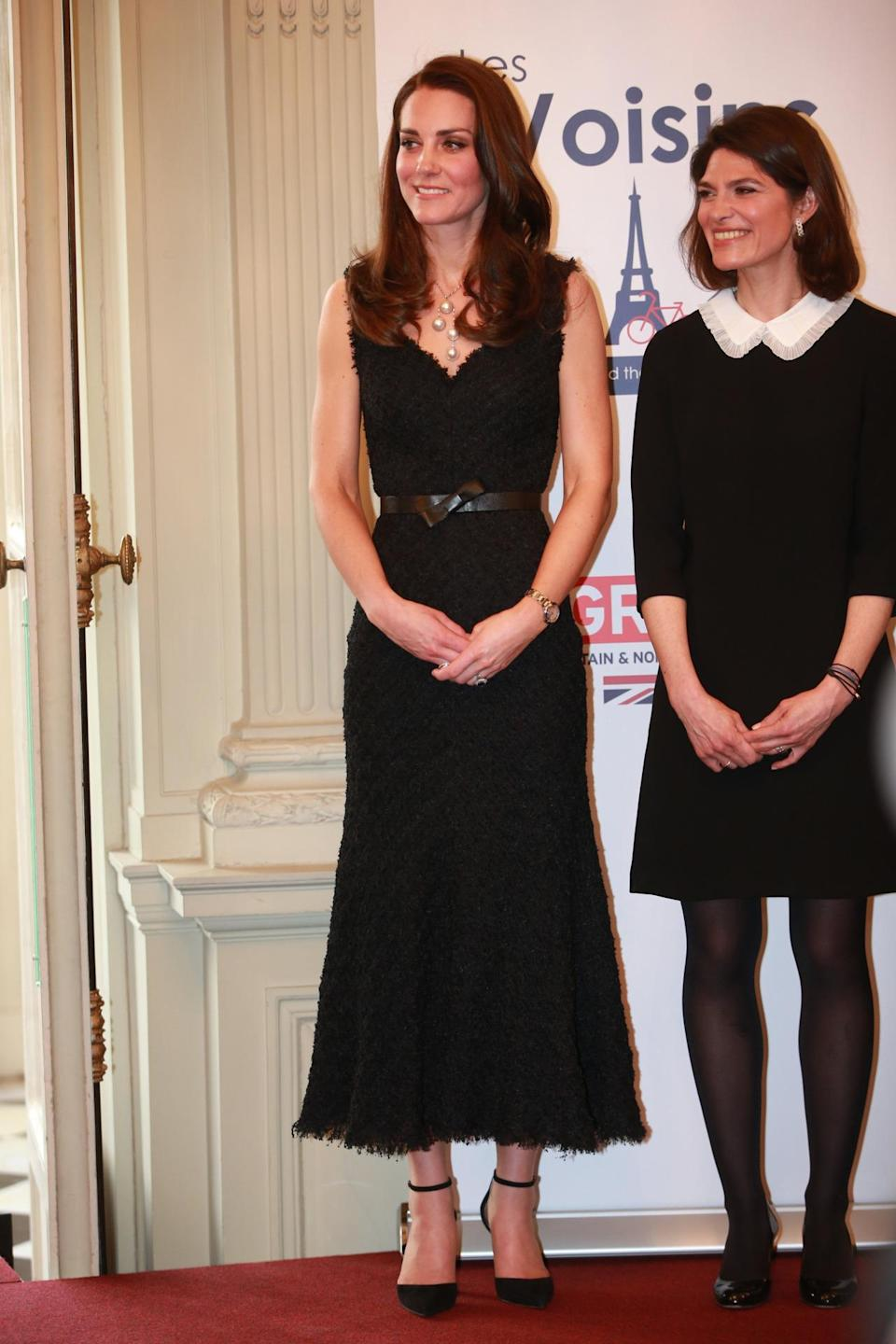 <p>For her arrival in Paris, Kate chose a textured black dress by trusted British label, Alexander McQueen. It was one of the few sleeveless designs the Duchess has donned over the years and appeared to be made from a fringed lace fabric. Kate's jewellery could not be ignored. Huge pearl Balenciaga earrings and a stand-out matching necklace added a nice touch to the elegant look which was finished off with suede Gianvito Rossi heels. </p><p><i>[Photo: PA]</i></p>