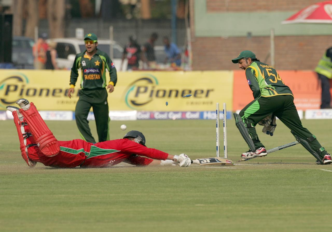 Zimbabwe captain Brendan Taylor (L) looses a wicket to Pakistan wicketkeeper Sarfraz Ahmed on August 31, 2013 during the third and final one-day international at the Harare Sports Club. AFP PHOTO / JEKESAI NJIKIZANA        (Photo credit should read JEKESAI NJIKIZANA/AFP/Getty Images)