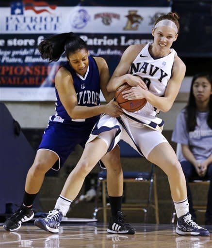 Navy forward Audrey Bauer, right, steals the ball from Holy Cross guard Brisje Malone during the first half of an NCAA college basketball game in the championship game of the Patriot League Conference tournament in Annapolis, Md., Saturday, March 16, 2013. (AP Photo/Patrick Semansky)