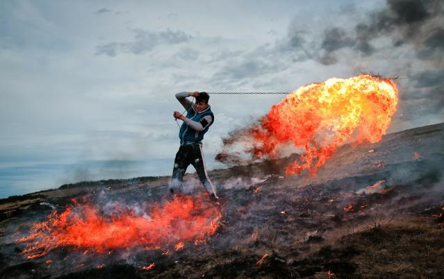 In this picture taken on Sunday, March 10, 2019, a young man spins a burning tire on a metal chain during a ritual marking the upcoming Clean Monday, the beginning of the Great Lent, 40 days ahead of Orthodox Easter, on the hills surrounding the village of Poplaca, in central Romania's Transylvania region. Romanian villagers burn piles of used tires then spin them in the Transylvanian hills in a ritual they believe will ward off evil spirits as they begin a period of 40 days of abstention, when Orthodox Christians cut out meat, fish, eggs, and dairy. (AP Photo/Vadim Ghirda)