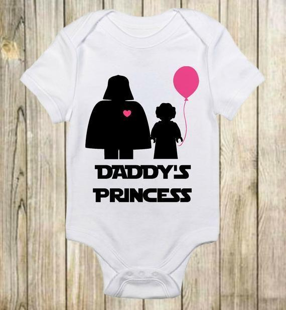 """<p><strong>ShowerTimeBabyWear</strong></p><p>etsy.com</p><p><strong>$13.00</strong></p><p><a href=""""https://go.redirectingat.com?id=74968X1596630&url=https%3A%2F%2Fwww.etsy.com%2Flisting%2F532598956%2Fdaddys-princess-star-wars-onesie-darth&sref=https%3A%2F%2Fwww.delish.com%2Fkitchen-tools%2Fcookware-reviews%2Fg29568867%2Fstar-wars-gifts%2F"""" rel=""""nofollow noopener"""" target=""""_blank"""" data-ylk=""""slk:BUY NOW"""" class=""""link rapid-noclick-resp"""">BUY NOW</a></p><p>It's never too early to turn them into a <em>Star Wars</em> fan.</p>"""