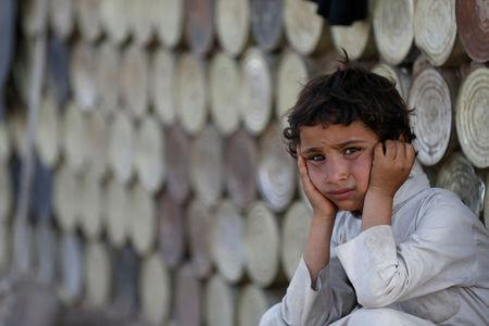 A boy looks on as he sits next to a hut at a camp for people displaced by the war near Sanaa, Yemen April 24, 2017. REUTERS/Khaled Abdullah