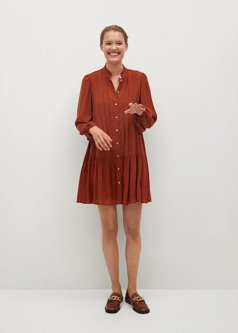 """<h2>Mango Pleated Detail Dress</h2><br>Run, don't walk, to throw this russet-hued dress over every autumnal separate you own. Whether it's canvas sailor dungarees, barrel-leg jeans, tailored trousers, or — <em>duh —</em> leggings, every pant in your wardrobe will play nice with this flowing tunic. (Which, of course, you can still wear as a leg-revealing dress when the occasion calls.)<br><br><strong>Mango</strong> Pleated detail dress, $, available at <a href=""""https://go.skimresources.com/?id=30283X879131&url=https%3A%2F%2Fshop.mango.com%2Fus%2Fwomen%2Fdresses-short%2Fpleated-detail-dress_77097905.html"""" rel=""""nofollow noopener"""" target=""""_blank"""" data-ylk=""""slk:Mango"""" class=""""link rapid-noclick-resp"""">Mango</a>"""