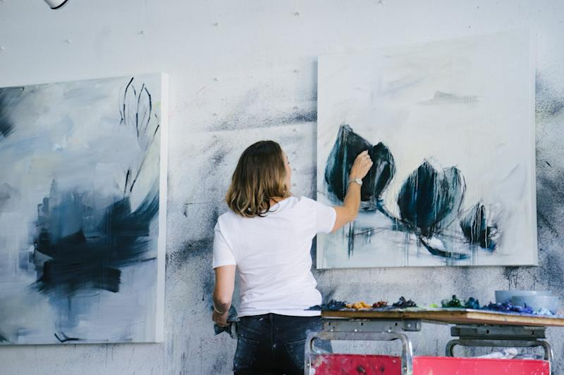 Artist mid-adult woman working in art studio, abstract oil paint on canvas.