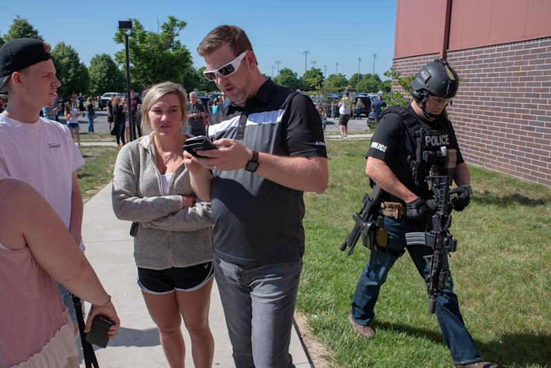 Parents wait while a SWAT officer passes outside Noblesville High School.