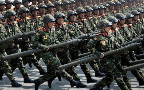Soldiers carrying rockets march across Kim Il Sung Square during a military parade - Credit: AP