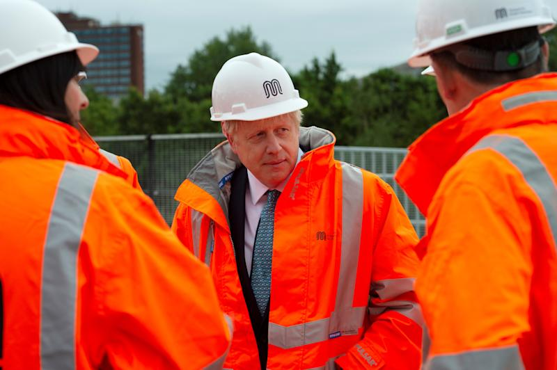 Britain's Prime Minister Boris Johnson reacts as he meets engineering graduates on the site of an under-construction tramline in Stretford, near Manchester, Britain July 27, 2019. Geoff Pugh /Pool via REUTERS