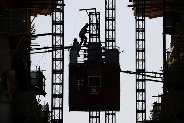 <p>Workers stand on the roof of an elevator at the construction site of a new financial district in Beijing, China May 23, 2017. (Photo: Thomas Peter/Reuters) </p>