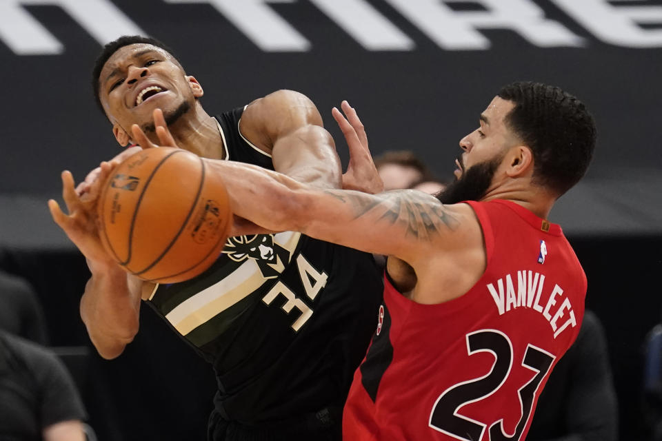 Toronto Raptors guard Fred VanVleet (23) fouls Milwaukee Bucks forward Giannis Antetokounmpo (34) during the second half of an NBA basketball game Wednesday, Jan. 27, 2021, in Tampa, Fla. (AP Photo/Chris O'Meara)