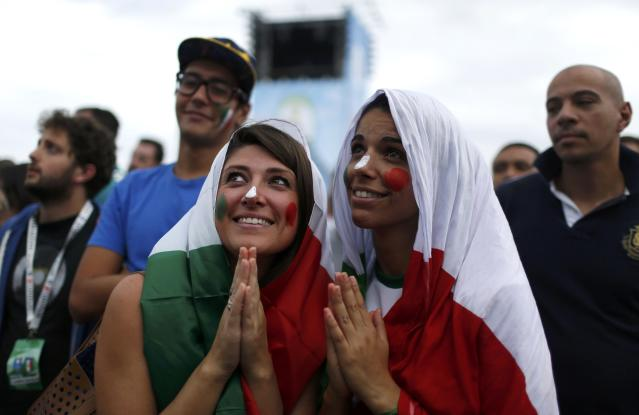 Italian soccer fans pretend they are praying while they watch the 2014 World Cup soccer match between Costa Rica and Italy on a large screen at Copacabana beach in Rio de Janeiro, June 20, 2014. REUTERS/Pilar Olivares (BRAZIL - Tags: SOCCER SPORT WORLD CUP)