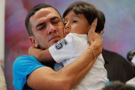 Javier, a 30-year-old from Honduras, holds his 4-year-old son William during a media availability in New York after they were reunited after being separated for 55 days following their detention at the Texas border, July 11, 2018. REUTERS/Lucas Jackson