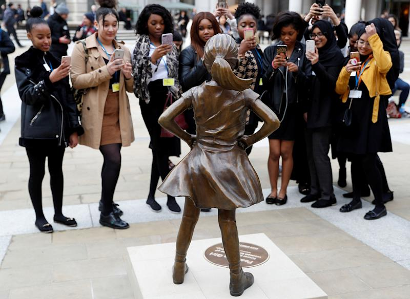 Students from some of London's all girls' schools, take pictures of the 'Fearless Girl' statue unveiled by State Street in the financial district of London, Britain, March 5, 2019. (Photo: Peter Nicholls/Reuters)