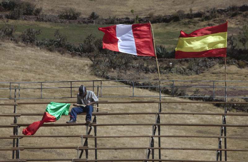"In this July 16, 2013 photo, an employee fixes a makeshift flag pole with a representation of Portugal's national flag attached, as representations of national flags from Peru and Spain flutter in the wind, before the start of a ""fiesta taurina,"" or a bullfighting event in Lachaqui, Peru. In the Peru of rugged mountains and unknown backwater corridas the Spanish tradition is as alive as ever, the bulls have no pedigree and getting gored is best avoided because hospitals are scarce. (AP Photo/Martin Mejia)"