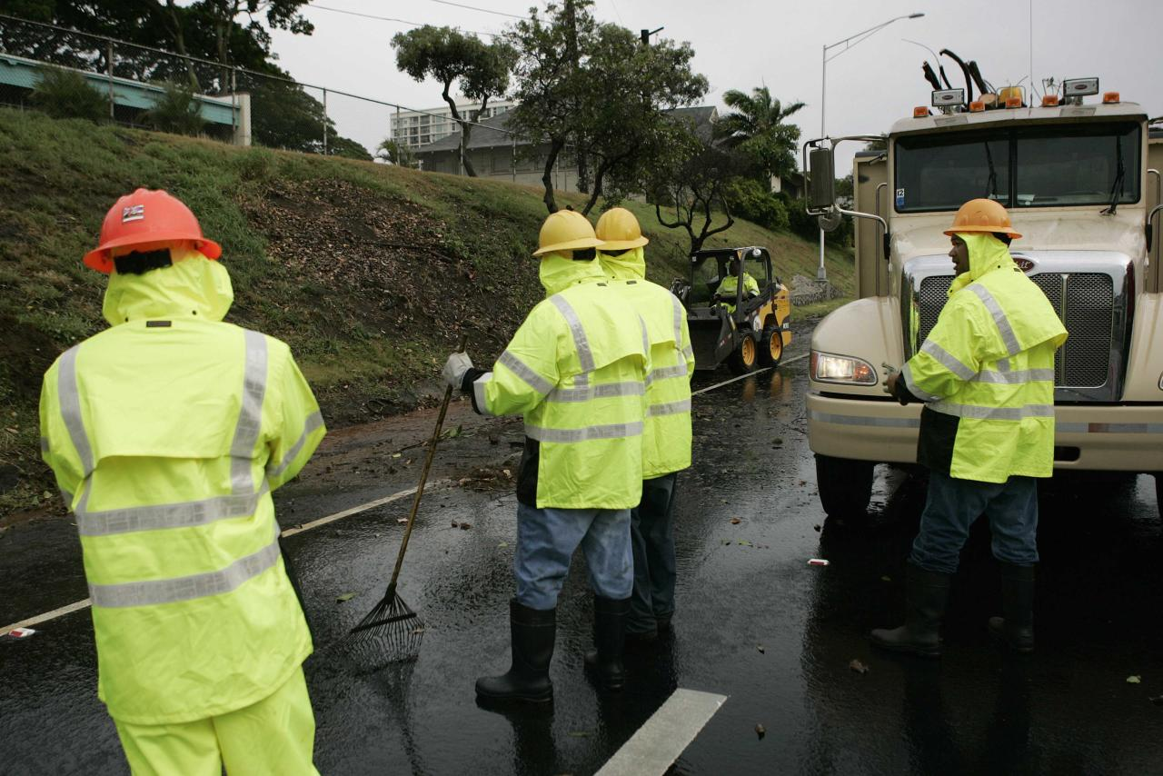 An emergency road crew clears off debris from a downed tree from the H1 freeway as Tropical Storm Iselle passes through the Hawaiian islands, in Honolulu, Hawaii, August 8, 2014. The center of Tropical Storm Iselle made landfall on Hawaii's Big Island on Friday, bringing strong winds and heavy rain, knocking down trees and causing power outages ahead of a more powerful storm gathering strength behind it. REUTERS/Hugh Gentry (UNITED STATES - Tags: ENVIRONMENT)