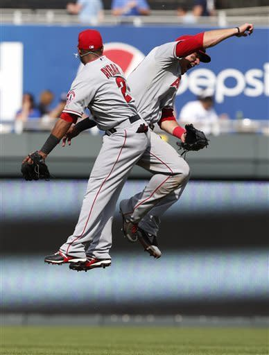 Los Angeles Angels shortstop Erick Aybar (2) and center fielder Mike Trout celebrate following a baseball game against the Kansas City Royals at Kauffman Stadium in Kansas City, Mo., Sunday, May 26, 2013. The Angels defeated the Royals 5-2. (AP Photo/Orlin Wagner)