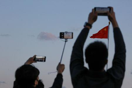 People take pictures of the lowering ceremony of the Chinese national flag that is held daily at sunset in Tiananmen Square in Beijing, China May 19, 2019. Picture taken May 19, 2019.  REUTERS/Thomas Peter