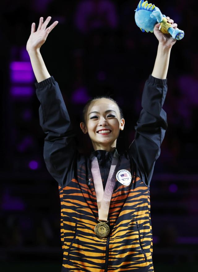 Rhythmic Gymnastics - Gold Coast 2018 Commonwealth Games - Individual Ribbon Final - Coomera Indoor Sports Centre - Gold Coast, Australia - April 13, 2018. Kwan Dict Weng of Malaysia poses with her gold medal. REUTERS/David Gray