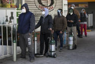 People line up with empty oxygen tanks to refill for family members sick with COVID-19 outside an oxygen store where dozens wait their turn in Mexico City, Thursday, Dec. 31, 2020. (AP Photo/Marco Ugarte)