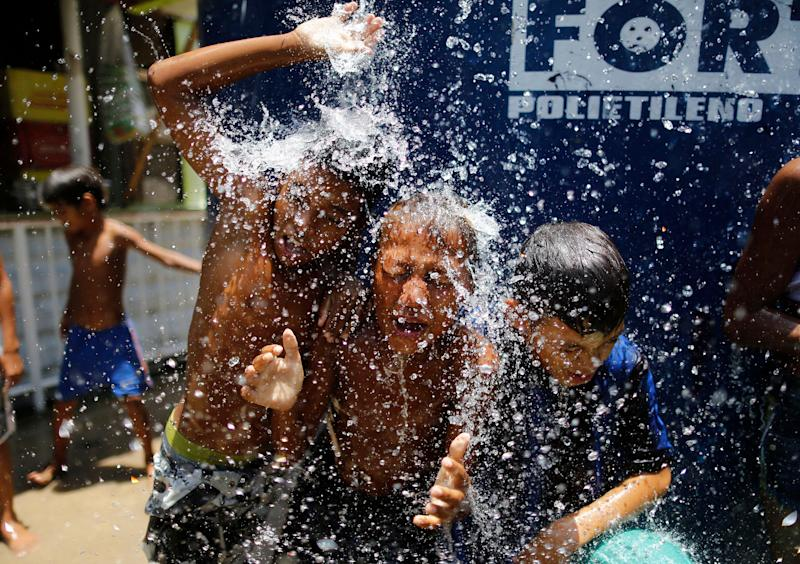 """Children play under the water from a water tank at the Alemao Complex neighborhood in Rio de Janeiro in January 2015. According to state environment secretary Andre Correa, the region was """"experiencing the worst water crisis in its history."""" (Photo: AP Photo/Leo Correa)"""