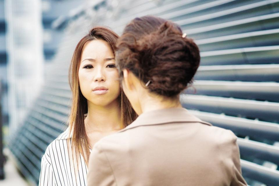 Serious young woman being scolded by her female boss.