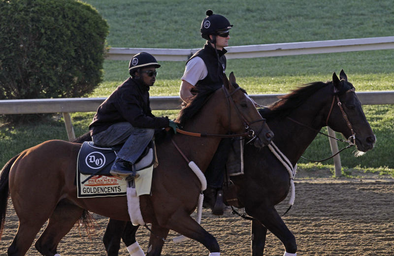 Preakness Stakes entrant Goldencents with jockey Kevin Krigger aboard, walks the track at Pimlico Race Course Friday, May 17, 2013 in Baltimore. At right on the pony is assistant trainer Jack Sisterson. The Preakness Stakes horse race is scheduled for Saturday. (AP Photo/Garry Jones)