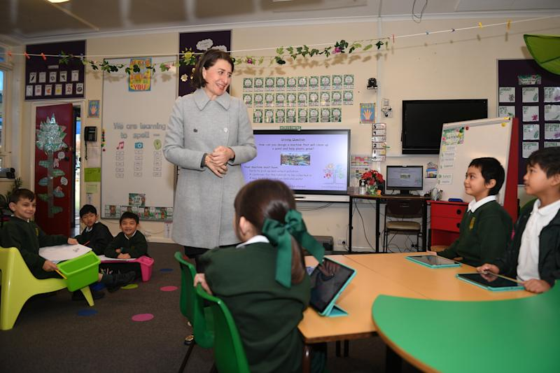 Pictured is Gladys Berejiklian in a grey coat in a classroom with young students in green uniforms.