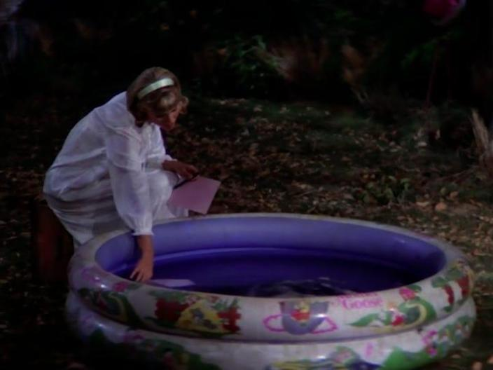 sandy dunking her hand in a blow-up kiddie pool