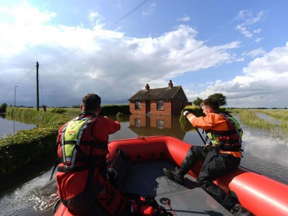 Rescue workers in Wainfleet after the River Steeping breached its banks (PA)