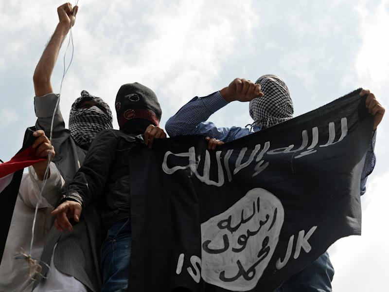 Kashmiri demonstrators hold up a flag of the Islamic State of Iraq and the Levant (ISIL) during a demonstration in downtown Srinagar on July 18, 2014