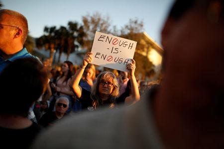 FILE PHOTO - A woman holds a placard during a candlelight vigil for victims of the shooting at Marjory Stoneman Douglas High School, in Parkland, Florida, February 15, 2018. REUTERS/Carlos Garcia Rawlins