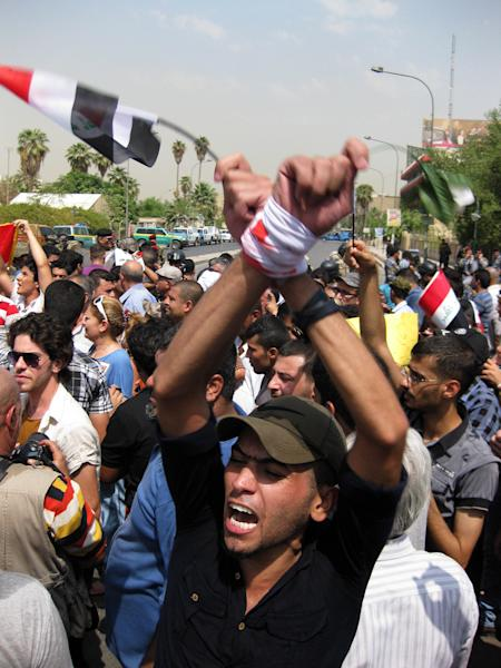 Protesters chant slogans against the Iraqi parliament in Baghdad, Iraq, Saturday, Aug. 31, 2013. Protesters held rallies in Baghdad and the southern Iraqi city of Basra to demand to cancel parliamentarians' pensions. (AP Photo/ Khalid Mohammed)