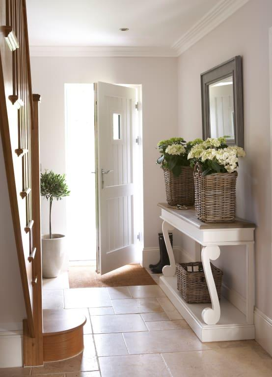 <p>White walls, smooth floor tiles and an understated approach to furnishing has absolutely created the ideal hallway here and with some fresh blooms in place, we bet it smells as good as it looks as well, which is great in a high-traffic area.</p>  Credits: homify / Emma & Eve Interior Design Ltd