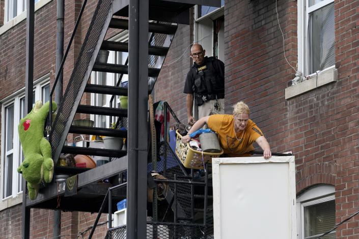 Kristen Bigogno tosses some of her belongings off a balcony as a member of the St. Louis Sheriff's Department watches as Bigogno is evicted from her home Friday, Sept. 17, 2021, in St. Louis. Bigogno is among thousands of Americans facing eviction now that the national moratorium has ended. (AP Photo/Jeff Roberson)