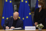 European Council President Charles Michel signs the EU-UK Trade and Cooperation Agreement at the European Council headquarters in Brussels, Wednesday, Dec. 30, 2020. European Union's top officials have formally signed the post-Brexit trade deal sealed with the United Kingdom. European Commission president Ursula von der Leyen and European Council president Charles Michel put pen to paper on Wednesday morning during a brief ceremony in Brussels (Johanna Geron, Pool Photo via AP)