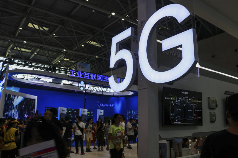 In this Tuesday, Aug. 27, 2019, photo, visitors tour an exhibitor booth with a 5G on display at the Smart China Expo in southwest China's Chongqing Municipality. The World Bank and a Chinese Cabinet agency have urged Beijing to roll back plans for government-led technology development that are fueling a tariff war with Washington. (Chinatopix via AP)