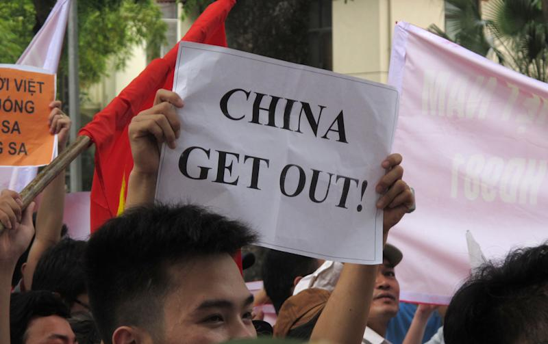 A Vietnamese protester holds a banner in a rally against Beijing's deployment of an oil rig in the contested waters of the South China Sea, outside the Chinese Embassy on Sunday, May 11, 2014 in Hanoi, Vietnam. The deployment of the rig has a triggered a tense standoff in the ocean and raised fears of confrontation between the neighboring countries. (AP Photo/Chris Brummitt)