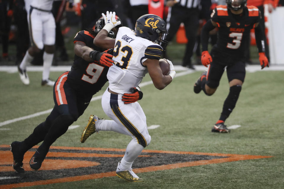 California running back Marcel Dancy (23) is brought down by Oregon State outside linebacker Hamilcar Rashed Jr. during the second half of an NCAA college football game in Corvallis, Ore., Saturday, Nov. 21, 2020. Oregon State won 31-27. (AP Photo/Amanda Loman)