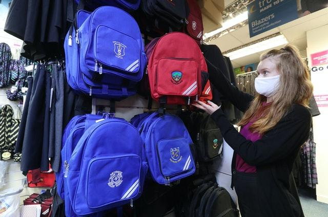 A worker hanging up school bags in a shop