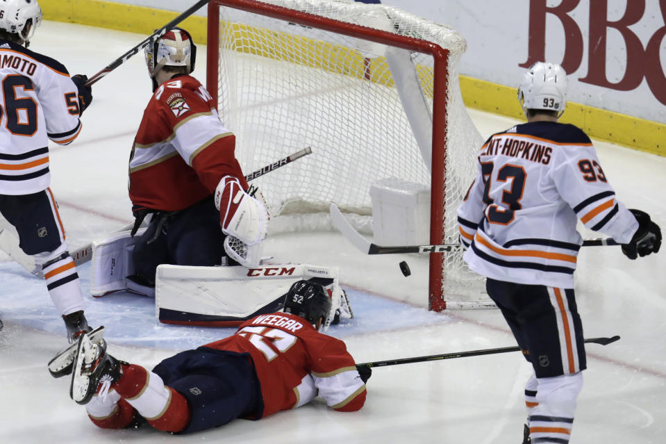 The puck gets past Florida Panthers goaltender Sam Montembeault, left, for a goal by Edmonton Oilers center Leon Draisaitl (not shown) during the third period of an NHL hockey game, Saturday, Feb. 15, 2020, in Sunrise, Fla. (AP Photo/Lynne Sladky)